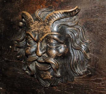 A Horned God, Satyr or perhaps Pan on the front of the chest. To me it looks like carved elm whereas the main body of the chest is clearly of oak.